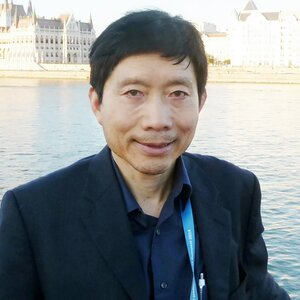 This photo is of Dr. Tim Liao. He is wearing a black sports coat over a navy blue shirt and standing in front of a river with buildings visible on the opposite bank.